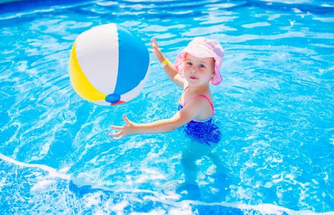 piscine avec enfant qui joue au ballon