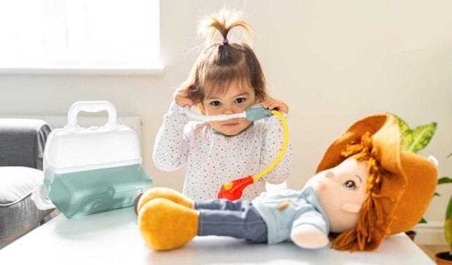 petite fille joue medecin valise docteur.