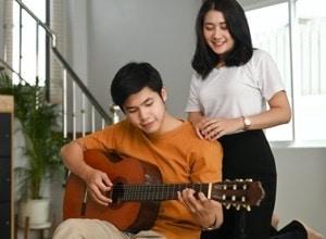 jeune joue à la guitare junior